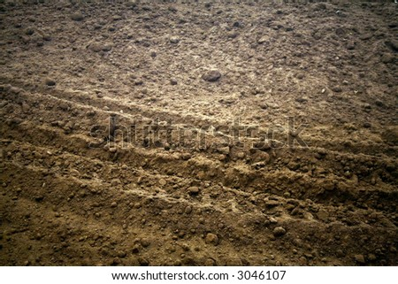 Dirt with a vehicle track running through it - stock photo