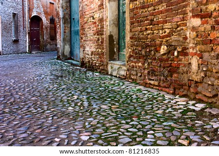 dirty alley in the old town with pavement of porphyry cobblestones - stock photo