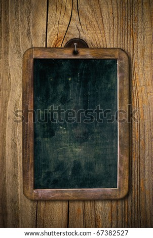 dirty and scratched wooden school slate over a wood wall, vertical image