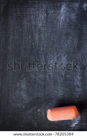 Dirty and used blackboard and a piece of colored chalk - stock photo