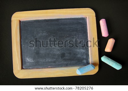 Dirty and used old slate and pieces of colored chalk - stock photo