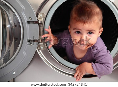 dirty baby inside a washer - stock photo