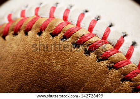 dirty baseball, white and brown against a dark background, close-up - stock photo
