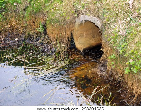 Dirty black waste waters flows from concrete pipe to river        - stock photo