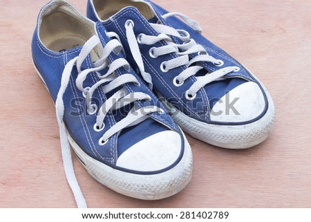 dirty blue shoes on the wood background