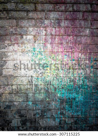 Dirty brick wall painted with spots of paint colors - stock photo