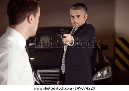 Dirty business. Confident mature men in formalwear aiming another men with gun - stock photo