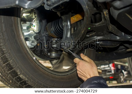dirty car mechanic hands examining car automobile at repair service station - stock photo