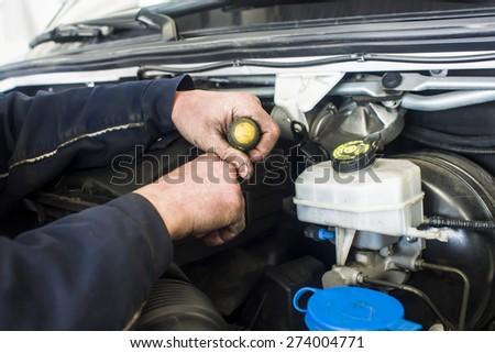 dirty car mechanic hands examining car automobile at repair service station - stock photo