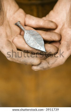 Dirty caucasian male metalmith's hands holding metal leaf.