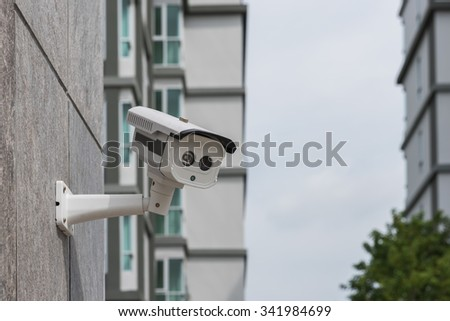 dirty CCTV security camera on stone wall - stock photo