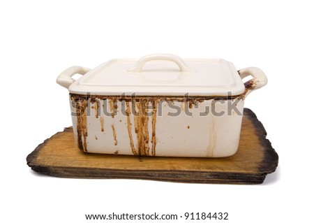 Dirty ceramic pot for stove on old kitchen board. - stock photo