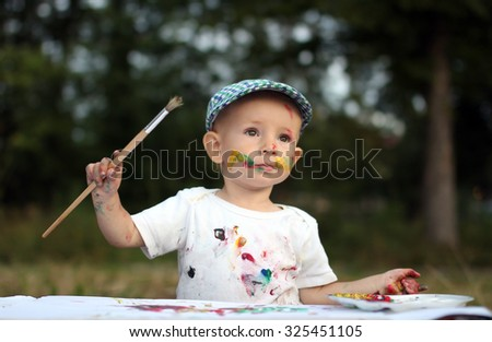 Dirty child painting outdoor - stock photo