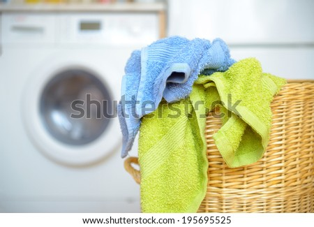 Dirty clothes basket with towels waiting for laundry with washing machine in backround - stock photo