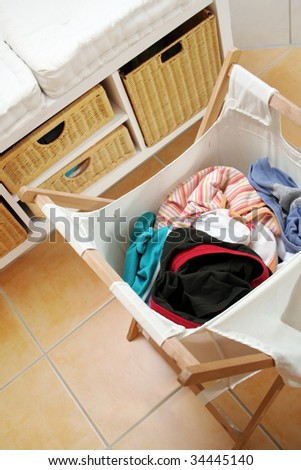 dirty clothes in a wooden laundry basket - stock photo
