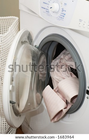 dirty clothes into the washing machine - stock photo