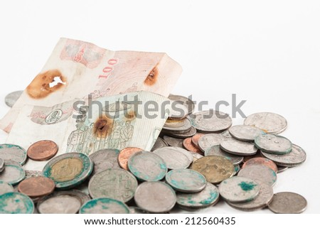 dirty coins and old banknote on white paper background