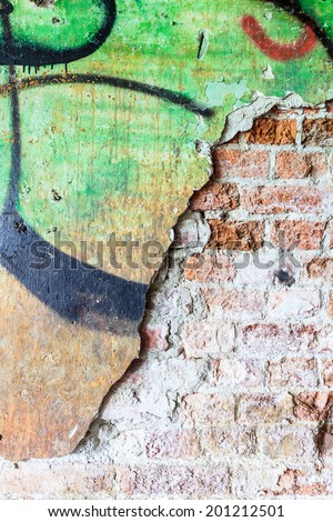 Dirty concrete wall with graffiti and big crack - stock photo