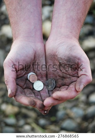 Dirty cupped hands holding few coins, high-angle close-up, concept of poverty, injustice, third world or low-paid hard work - stock photo