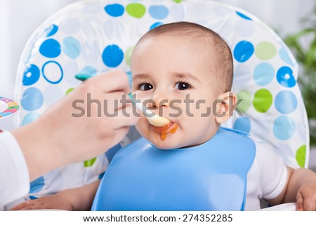 Dirty cute baby enjoy when eating food in kitchen - stock photo