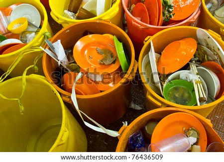 Dirty dishes, chopsticks, glasses and bowls in bins are waiting to be cleaned in a restaurant kitchen - stock photo