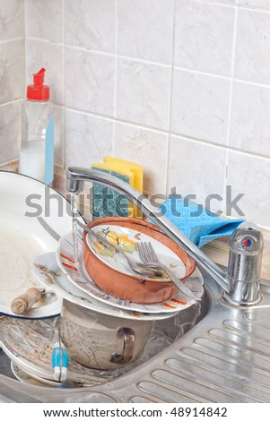 Dirty dishes in kitchen sink with running tap water - stock photo