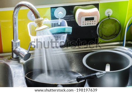 Dirty dishes in the sink  pots and tableware ready to wash - stock photo