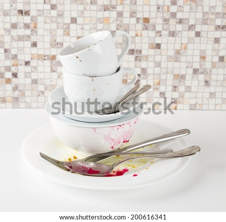 Dirty dishes on white kitchen table - stock photo