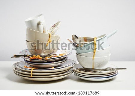 Dirty dishes pile needing washing up. Household chore concept on white background