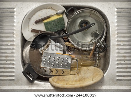 Dirty dishes, utensils in the metal sink background - stock photo