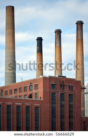 Dirty factory smoke stacks over an old brick building - stock photo