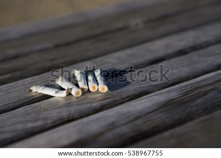 Dirty Fag end on wood bench,cigarette butts on wood floor