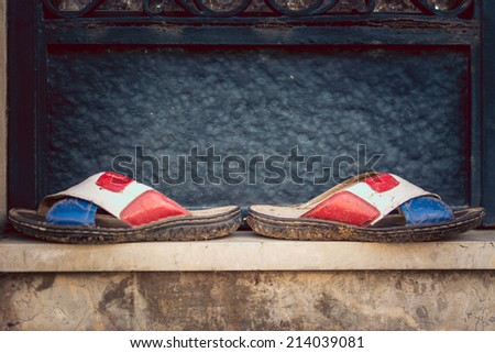 Dirty filip-flops standing in front of a dark door - stock photo
