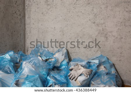 Dirty gloves employee . The repair process . Freed from the wall wallpaper . A  large pile of garbage and waste in blue bags. Restoring order. Concrete wall - stock photo
