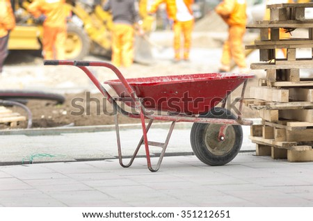 Dirty handcart standing on construction site, workers and machinery in background - stock photo