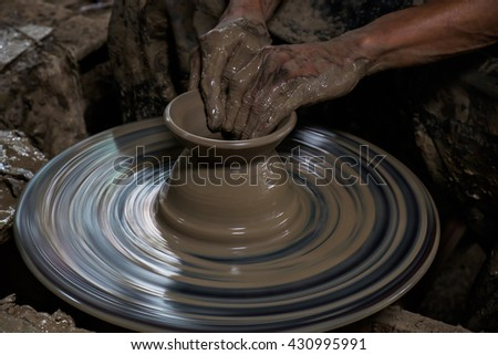 Dirty hands of a man making pottery from clay on wheel - stock photo