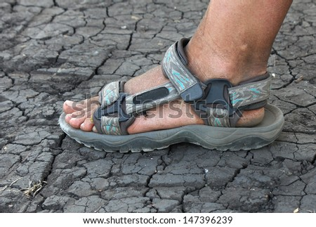 dirty human foot in sandals on the cracked earth  - stock photo