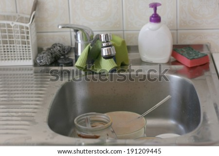Dirty kitchen sink with different old cleaning sponges, focus on tip of faucet - stock photo