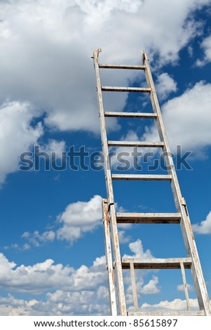Dirty ladder pointing to a blue cloudy sky