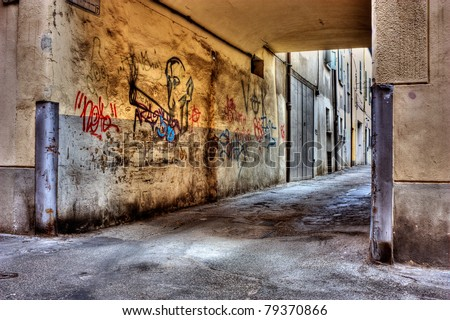 dirty lane in the old town, corner of narrow street, grunge wall with graffiti, draw of smoker of hashish, old passage with drawing of cannabis, drug addiction marijuana joint marijuana reefer spliff - stock photo