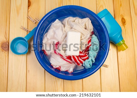 Dirty laundry in blue bowl with soap on wooden table - stock photo