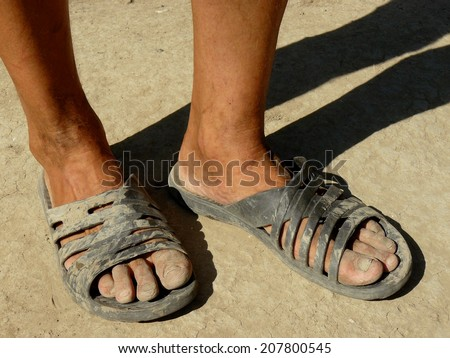 dirty male feet in rubber slippers on dried earth - stock photo