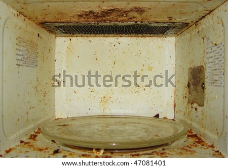 Dirty microwave. With burnt paint on the walls - stock photo