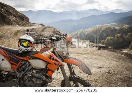 Dirty motorcycle motocross helmet on road - stock photo