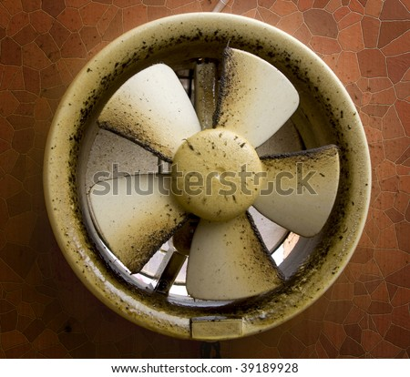 dirty oil stained kitchen exhaust fan on a mosaic wall