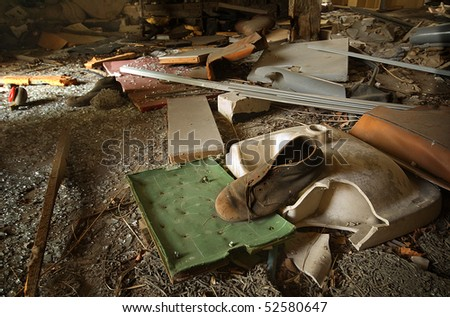 Dirty old boot laying in garbage on a soccer game board in an abandoned building. - stock photo