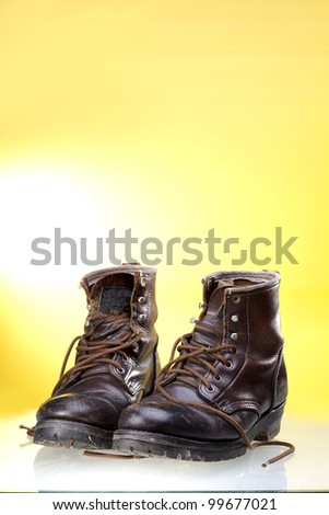 Dirty old boots leather isolated on yellow background