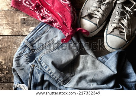 Dirty old jeans. sneakers and bandanna on floor - stock photo