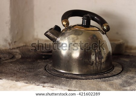 Dirty old kettle is boiling on firewood stove. - stock photo