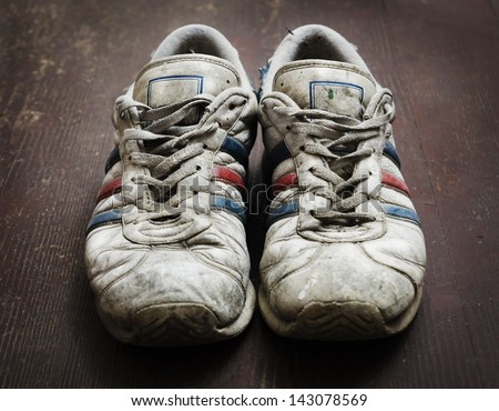 Dirty old shoes on wooden floor - stock photo